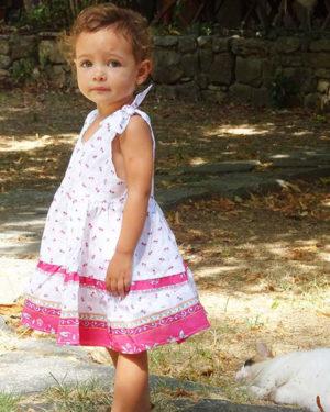 Robe Caline, au couleurs provençale et motifs. Se regle avec les noeuds sur les épaules. Enfant de 1 an à 12 ans, couleur blanc rose